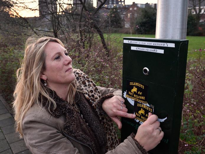 Esther Bikker verwijdert anti-islamstickers.