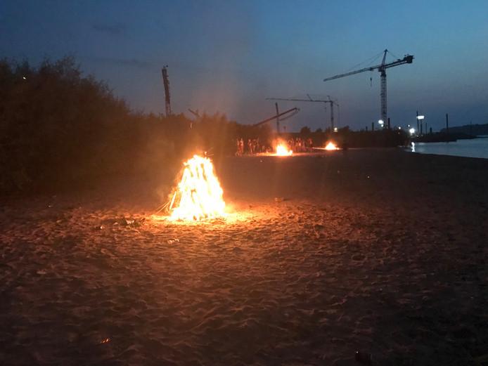 Jongeren staken op een waalstrandje in Druten onder andere pallets in brand.