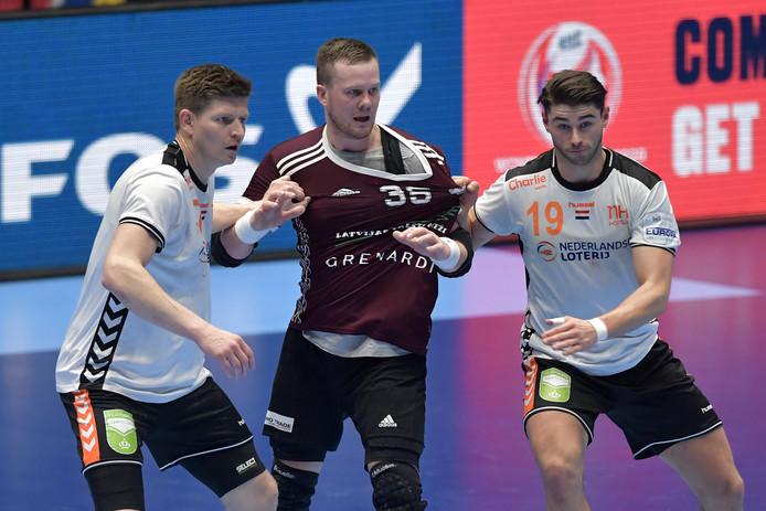 Nederland wint zijn eerste EK-wedstrijd met 32-24 van Letland. Egils Politers #35 (LAT) tussen Toon Leenders #7 (NED) en Robin Schoenaker #19 (NED) in.