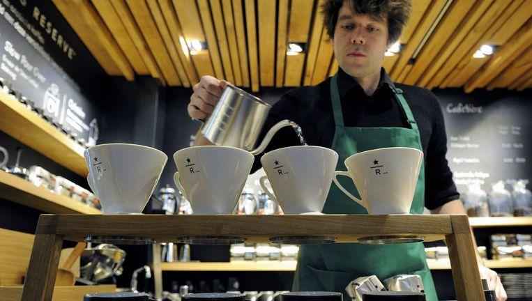 Een medewerker van een Starbucks-filiaal in Amsterdam. Beeld anp