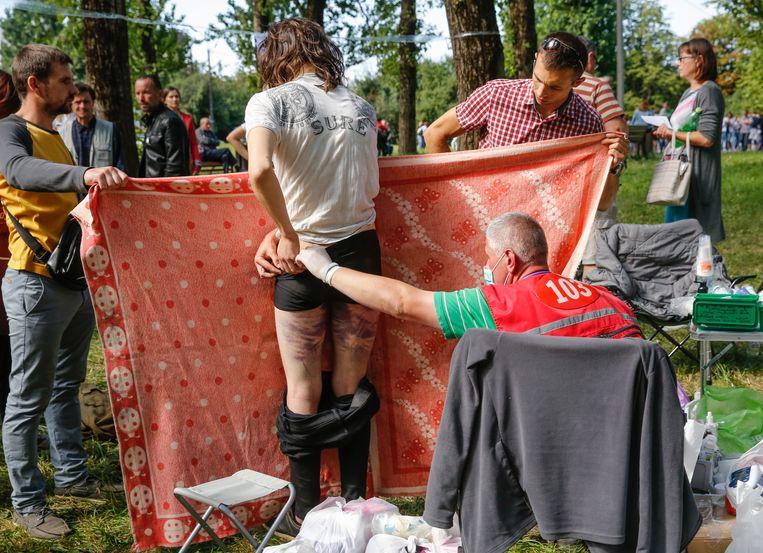 Mishandelde betogers worden in Minsk op verwondingen gecheckt door dokters. Beeld EPA