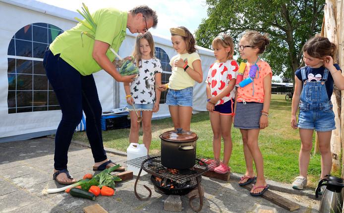 Kok Marijke Pool van Natuur en Zo maakt met Amsterdamse kinderen soep op een houtvuurtje bij camping Zonneweelde in Nieuwvliet.