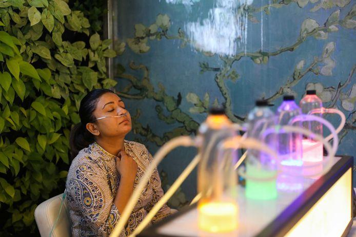 Une femme respire de l'air oxygéné en échange d'argent dans un bar prévu à cet effet, New Delhi, le 15 novembre 2019.