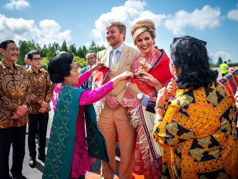 Bij aankomst op Sumatra krijgen koning Willem-Alexander en koningin Máxima een Ulos, een geweven deken die beschermt tegen de kou, omgehangen als welkom. Beeld ANP