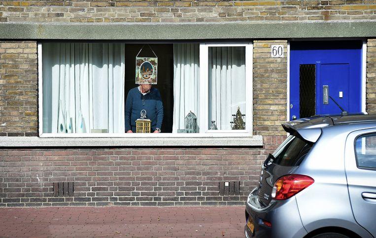 Een man, alleen, achter het raam van zijn huis in Den Haag. Beeld null