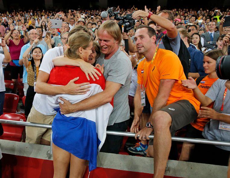 Dafne Schippers viert haar overwinning op de 200 meter tijdens het WK in 2015 met haar ouders en coach Bart Bennema. Beeld AP