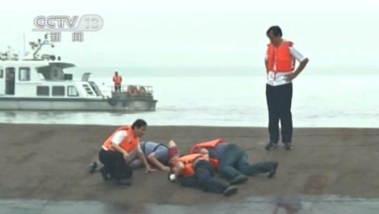 Reddingswerkers slaan met een hamer op de romp om te horen of er nog overlevenden in het schip zitten.