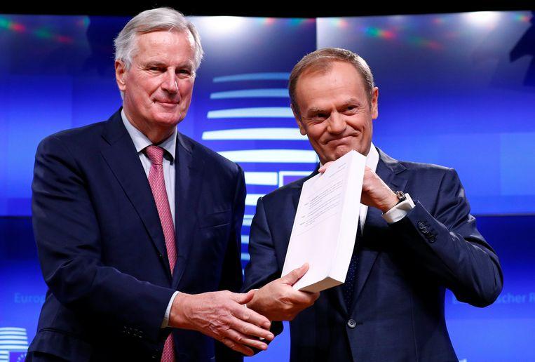Brexit-onderhandelaar voor de EU Michel Barnier en EU-president Donald Tusk met het ontwerpakkoord in Brussel op 15 november. Beeld REUTERS