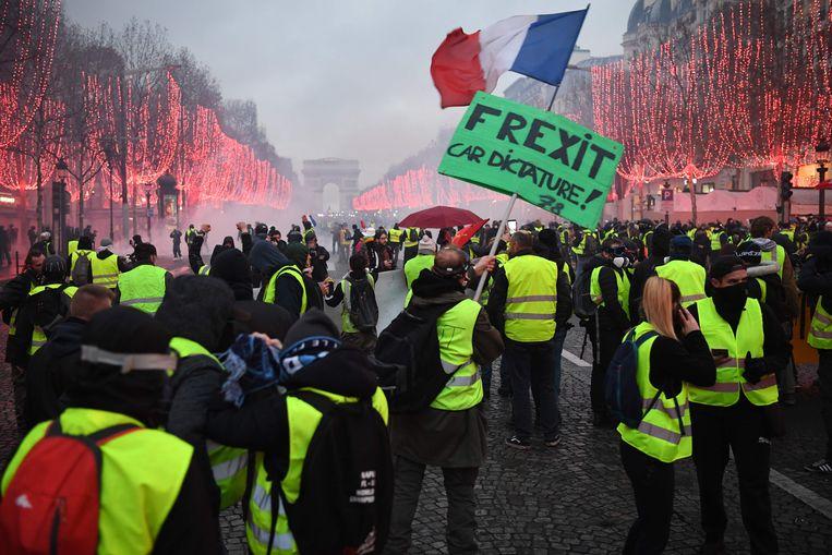 De 'gilets jaunes' op de Champs Elysees in Parijs  Beeld AFP