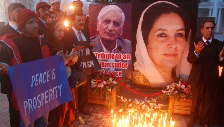Pakistanen branden kaarsjes ter herinnering aan Benazir Bhutto (rechts) Beeld ANP