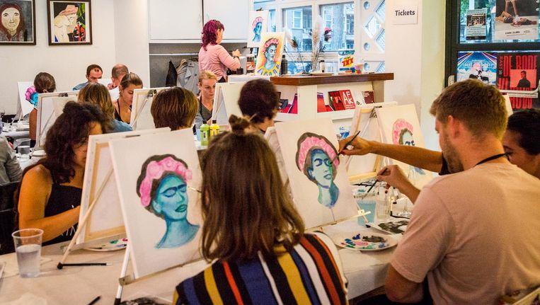 Deelnemers aan de workshop werken aan hun Kahloportretten. Beeld Tammy van Nerum