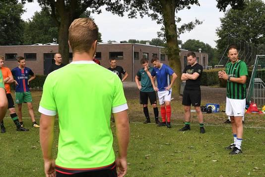 Trainer Michel Kuijpers (r) geeft zijn mannen uitleg.
