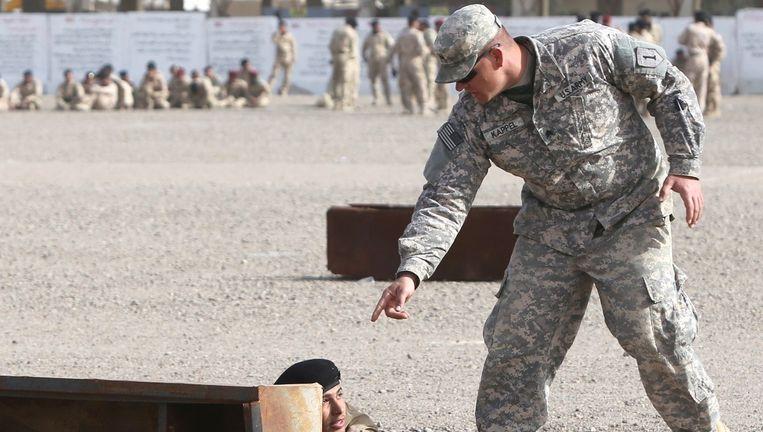 Een Amerikaanse soldaat traint een Iraakse soldaat nabij Baghdad in de strijd tegen IS. Het rapport roept de VS op om de leiding te blijven nemen in de strijd tegen het terrorisme.