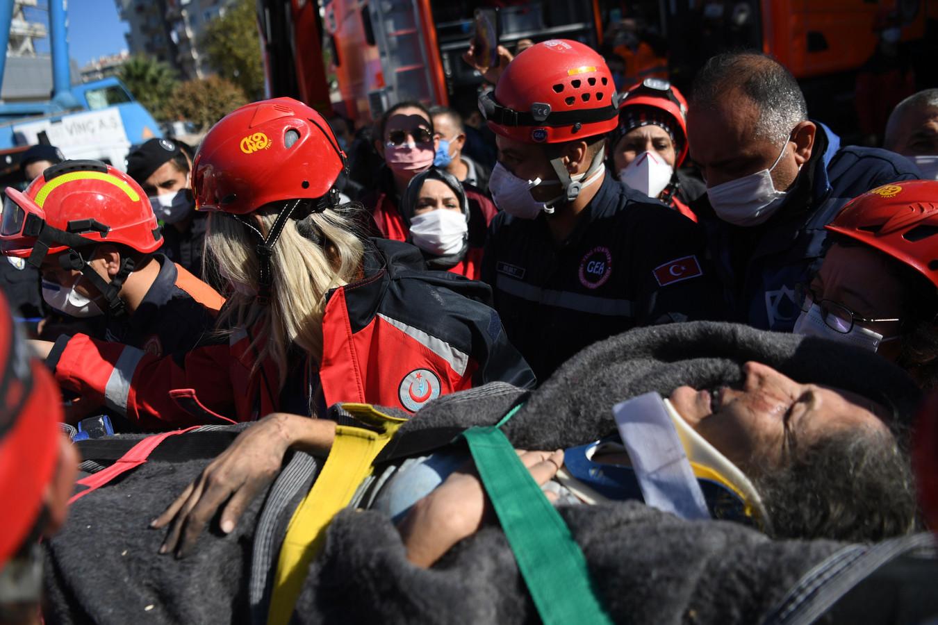Reddingswerkers brengen een onder het puin vandaan gehaalde vrouw in veiligheid.
