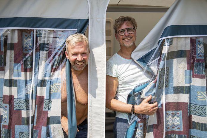 Amsterdammers Nick en Alexander (blauw shirt) Richardson bouwen hun voortent op bij Hoeve Springendal in Hezingen.