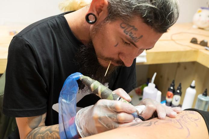 Juan Carlos Cordero zet een tattoo op het been van Agnieszka Lochert.