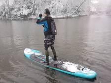 Deense studente glijdt ontspannen over water Slotvijver tijdens sneeuwbui