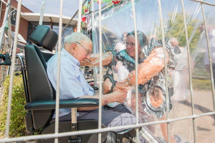 Schoondochter Erica Janse knuffelt schoonvader Krijn van Lieren (103) door het plastic.