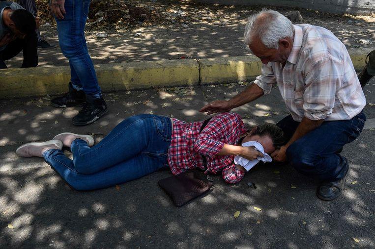 Een vrouw ligt bedwelmd door traangas op straat.