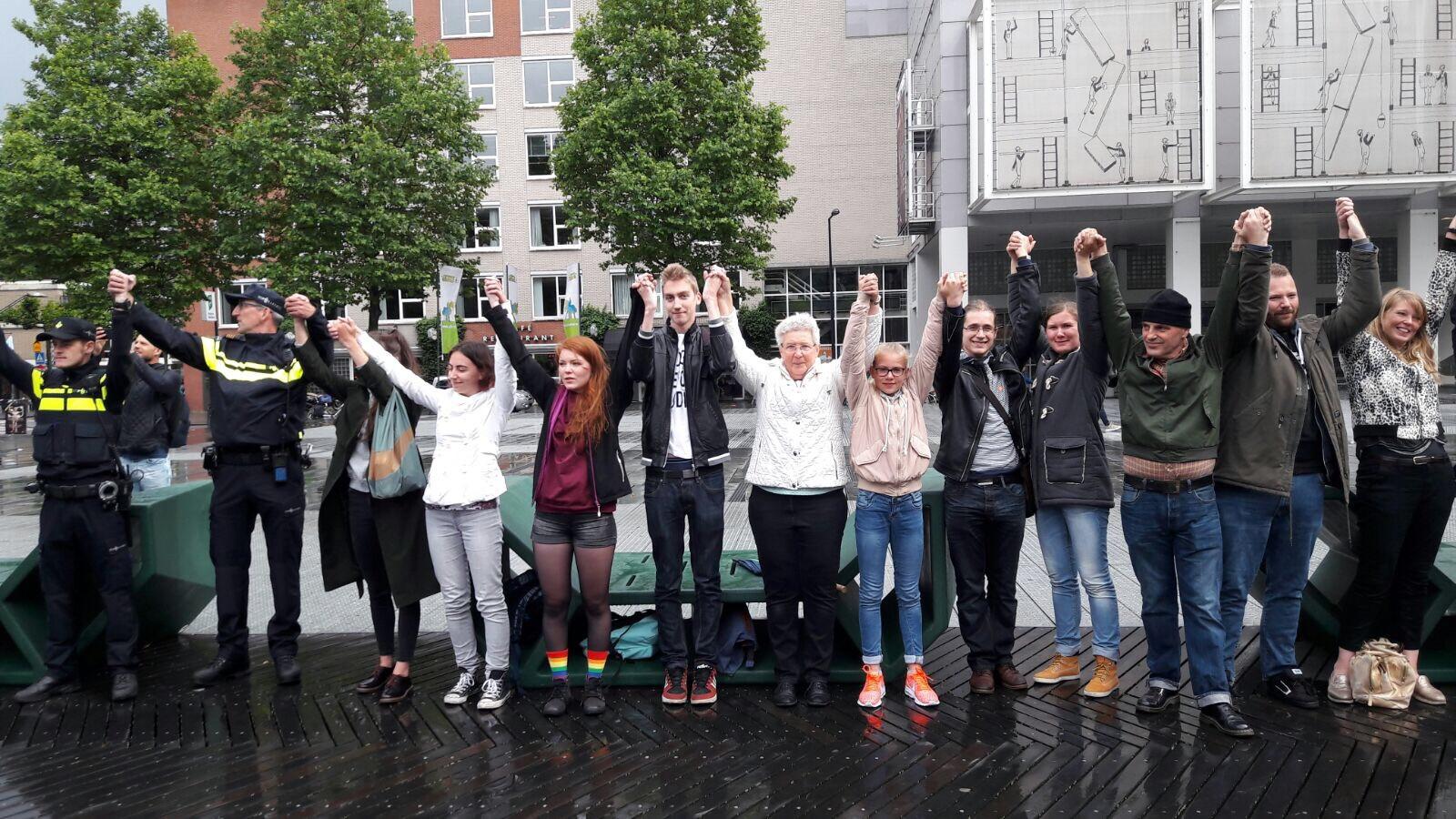 Hand in hand op het Schouwburgplein in Rotterdam na mishandeling van lesbisch stelletje.