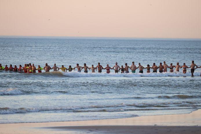 Omstanders zoeken samen met hulpdiensten bij de Zandmotor naar een vermiste zwemmer.