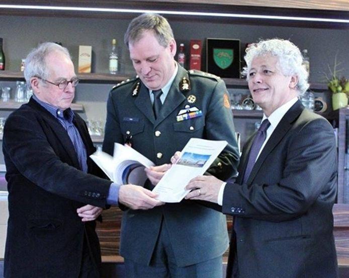Frans Adriaanse overhandigt kolonel Valk het onderzoek. Rechts burgemeester Ruud Severijns.