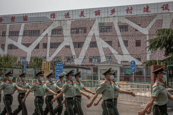 Chinese soldaten bewaken de gesloten Xinfadi-markt in Peking
