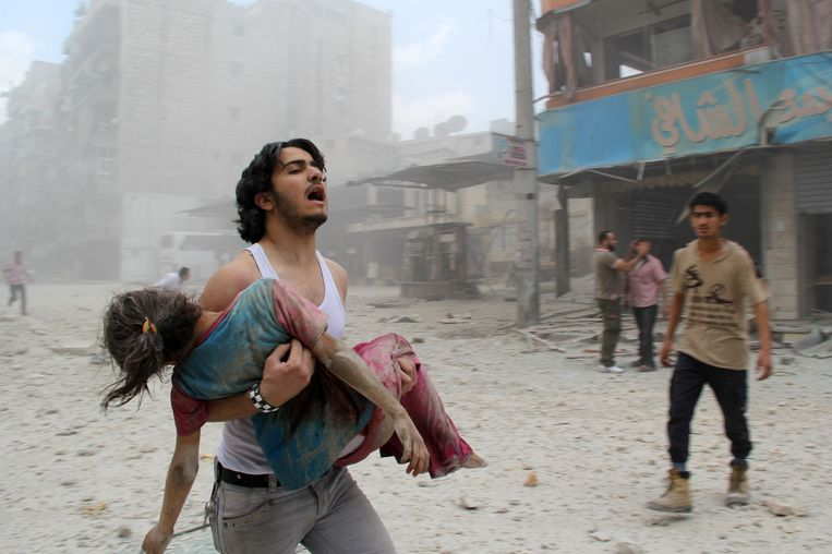 Een man draagt een jong meisjes dat gewond is geraakt door een vatenbom in het Kallaseh-district in Aleppo. Beeld afp