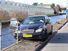 Auto balanceert na botsing op randje van sloot bij Nieuweweg in Honselersdijk