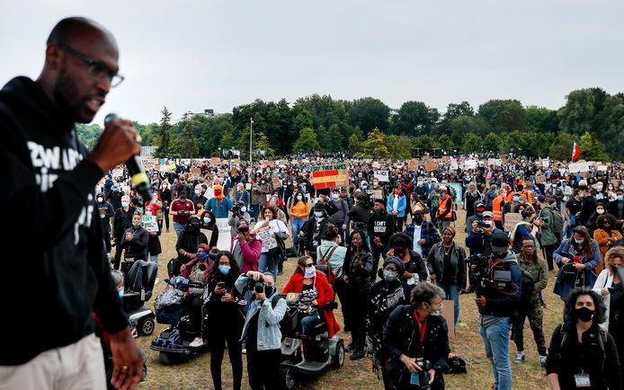 Demonstranten tijdens een demonstratie tegen racisme in het Nelson Mandelapark in de Bijlmer. Vooraan met microfoon: Mitchell Esajas.