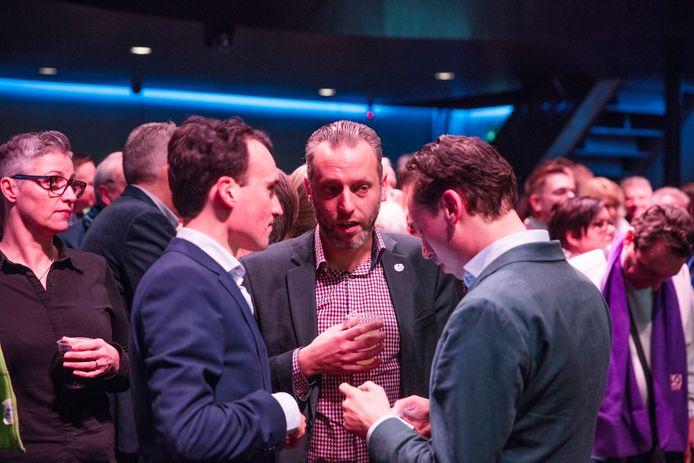 Paul Smeulders (links) in gesprek met SP-wethouder Erik de Vries (midden) tijdens de verkiezingsavond in Helmond.