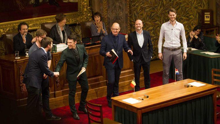 De vier finalisten samen met de presentatoren tijdens het Groot Dictee der Nederlandse Taal in de Vergaderzaal van de Eerste Kamer. Beeld anp