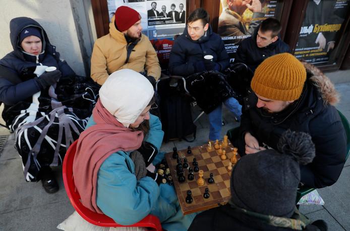 Klanten doen een schaakpartijtje voor de winkel in Moskou.