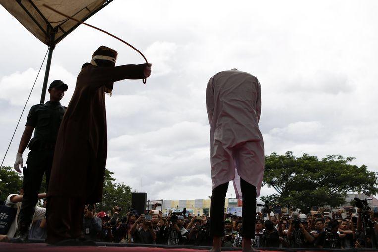 Een man die beschuldigd werd van homoseksualiteit krijgt een openbare afranseling in Atjeh. Beeld EPA