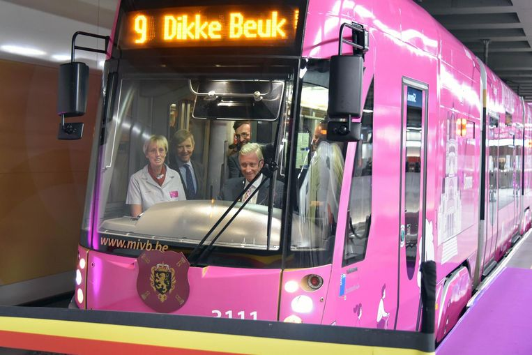 Onze vorst bestuurt een tram die een lint met de Belgische driekleur doorsnijdt.