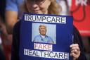 Een betoger houdt  een bord vast met: 'Trumpgezondheidszorg, neppe gezondheidszorg' tijdens een demonstratie