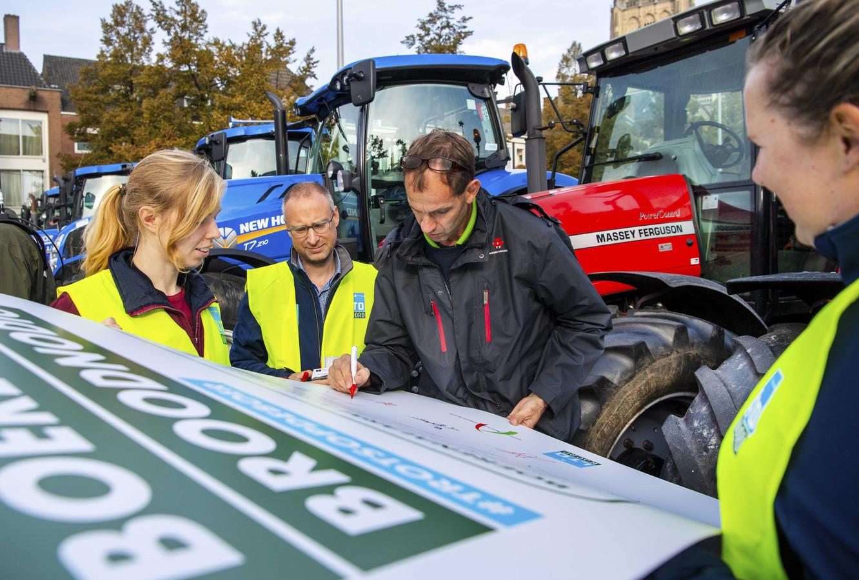 Boeren tekenen een manifest tijdens een demonstratie bij het provinciehuis van Gelderland.