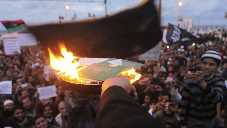 Betogers in Benghazi verbranden exemplaren van Kaddafi's groene boekje. Beeld reuters