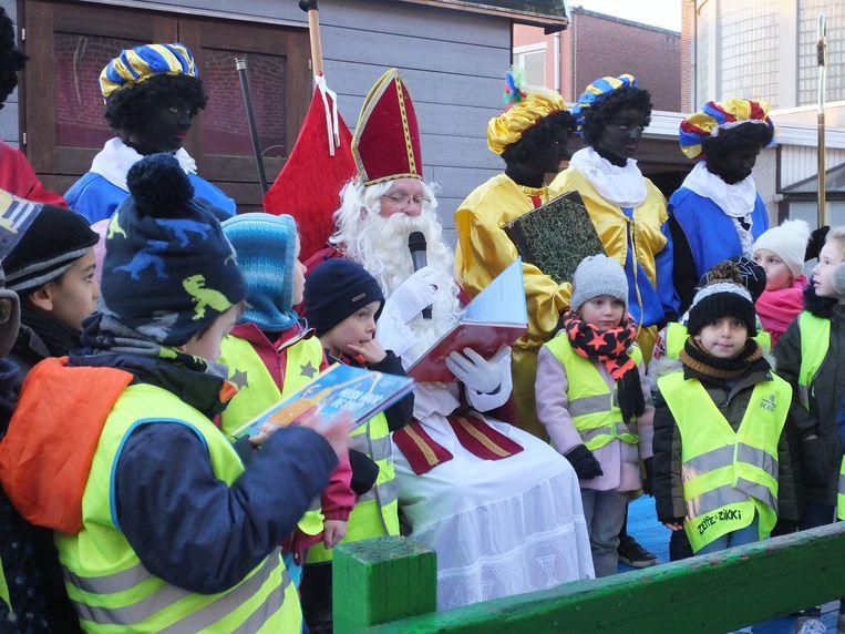 Sinterklaas leest voor uit zijn redelijk groot sprookjesboek.