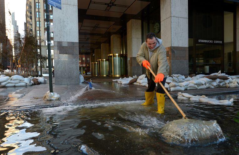 Een werkman duwt het water weg bij een gebouw aan Wall Street. Beeld EPA
