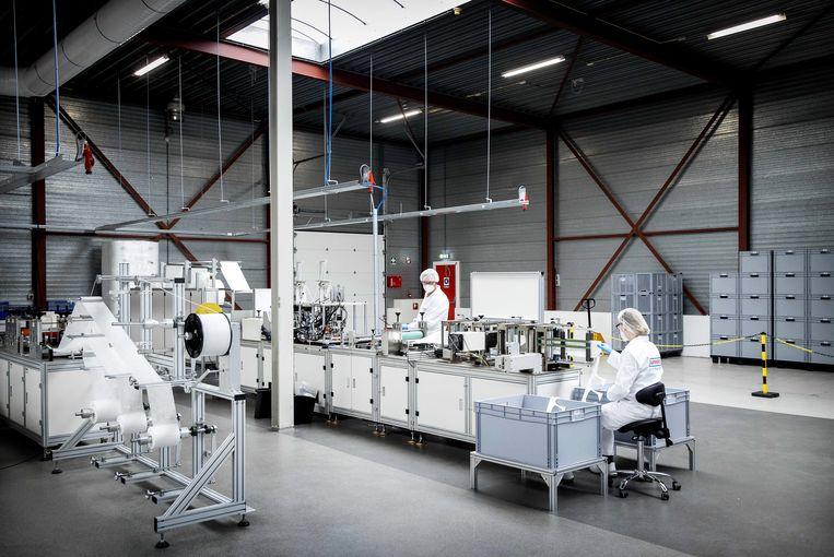De mondkapjesmachine van Afpro, dertig meter lang, in de fabriek bij Alkmaar.  Beeld EPA