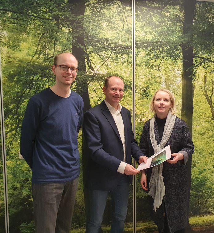 De broers Maurits en Martijn Groot Kormelink overhandigen het eerste exemplaar van Sabine Karssen van uitvaartzorg Troostrijk uit Ede