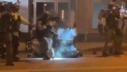 Amerikaanse agent hakt met schild in op betoger die op grond ligt