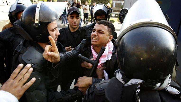 Egyptische ordetroepen houden een betoger aan tijdens de protesten vandaag in Caïro Beeld ap