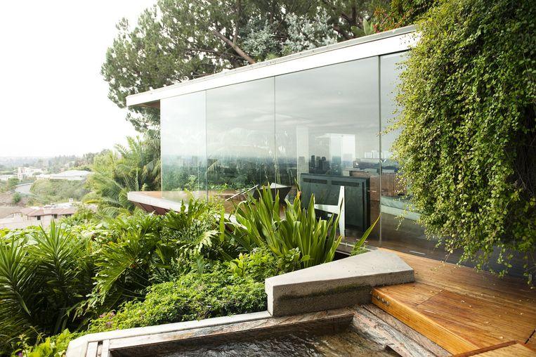 Buiten: Ver van de drukte van de stad ligt het huis in een tropische tuin. De glazen wanden en de natuur buiten maken het huis licht en doen ruimten nog groter lijken dan ze al zijn. Beeld Els Zweerink