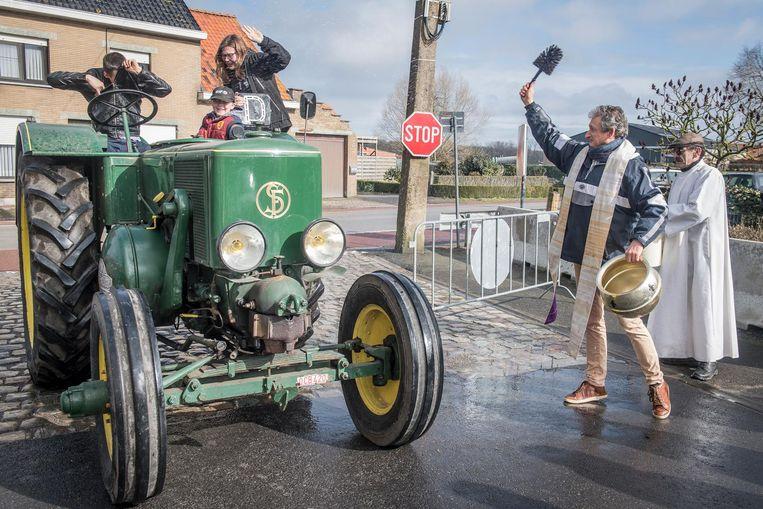 Pastoor Luc Brutin wijdt enthousiast een tractor. Iets té enthousiast misschien, aan de opzittenden te zien.