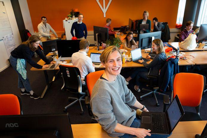 TU-student Japer Veen van de website gewoonmensendiemensenwillenhelpen.nl. Achter hem zijn collega's die hard bezig zijn vraag en aanbod aan elkaar te koppelen.