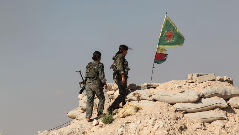 In de Syrische stad Kobani wappert de vlag van de YPG boven de stad. Beeld getty