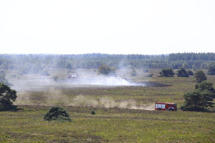 De brandweer aan het werk bij de bestrijding van de brand op de heide bij Elspeet.