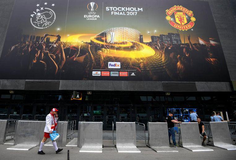 Een Ajax-fan loopt langs het voetbalstadion in Stockholm waar morgen de finale wordt gespeeld. Beeld epa